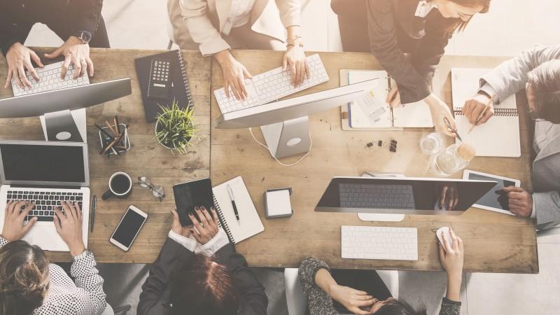 Büroalltag Kommunikation viele Personen mit verschiedenen Smart Devices und Kommunikationsmitteln