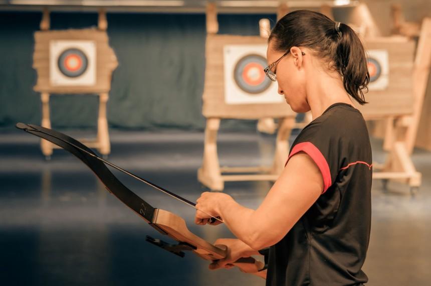 Indoor Bogenschießen Frau bereitet Pfeil und Bogen vor