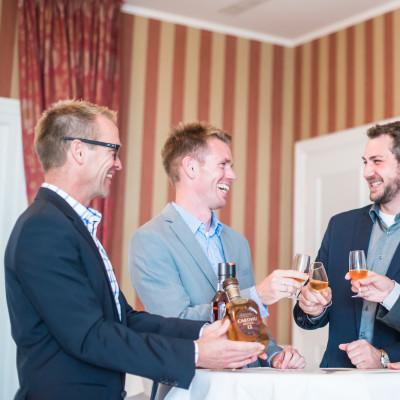 Whisky Tasting fröhliche Gruppe trinkt Whisky und stößt an