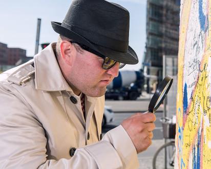 Ermittler Hut Trenchcoat Lupe Mauer Graffiti