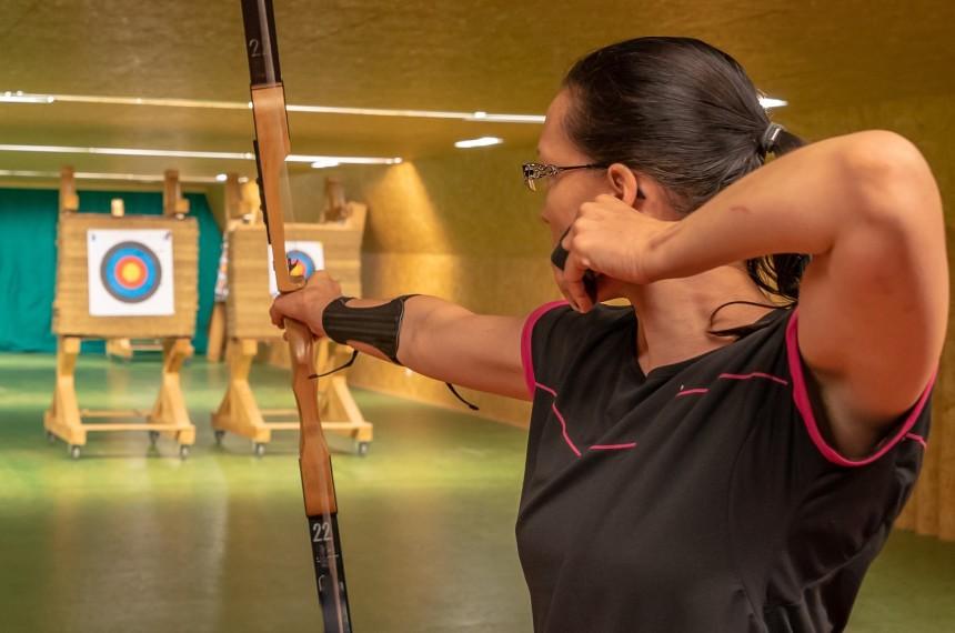 Bogenschießen Indoor Frau zielt mit Pfeil und Bogen auf Zielscheibe