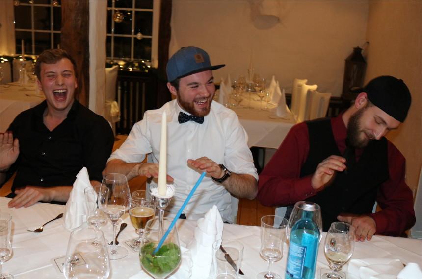 Drei Männer lachen beim Trommeln auf dem Tisch