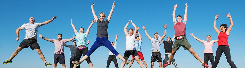 Team in Sportkleidung springt in die Luft