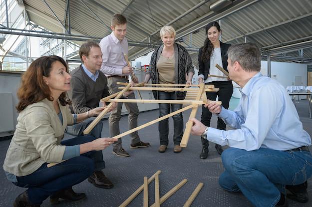 Leute bauen eine Brücke aus Brettern