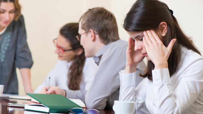 frau krank durch arbeit kopfschmerzen am konferenztisch