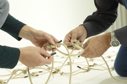 Zwei Paar Hände bauen ein Netz-Trier