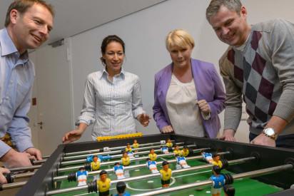 Vier Personen spielen Kicker und zwei Personen gucken zu