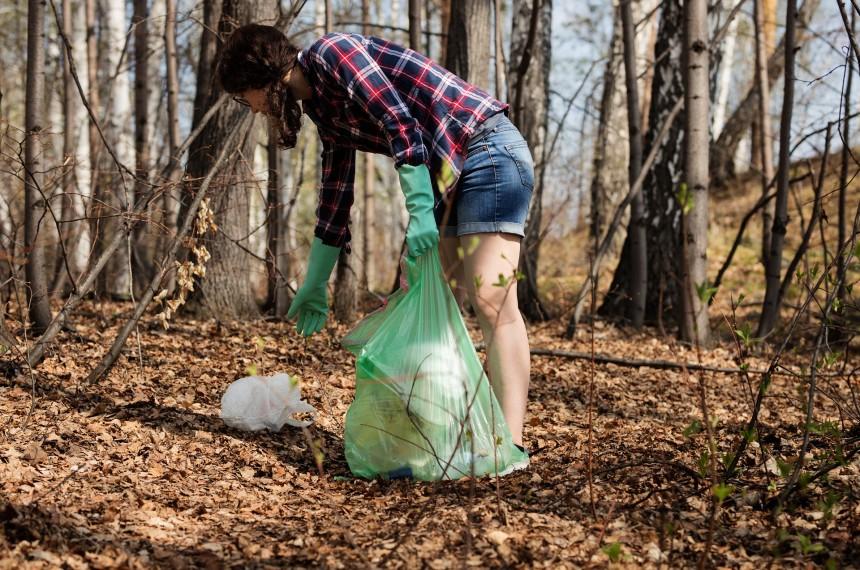 Junk Run Frau hebt beim Plogging Müll auf